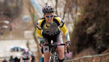 Anne-Marie Alderson riding a bike up a hill in a race.
