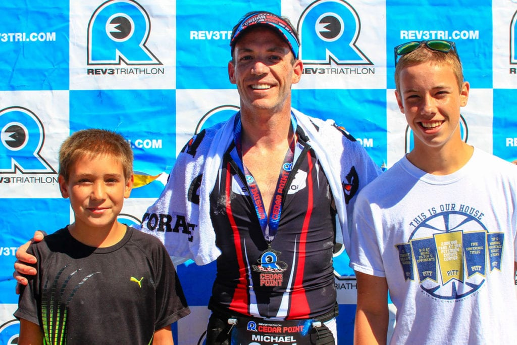 Mike Bauer with two kids and medal