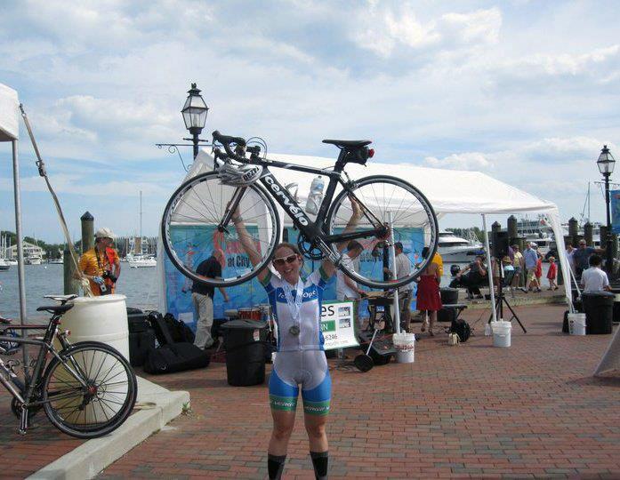 Sara Harper raising her bicycle above her head