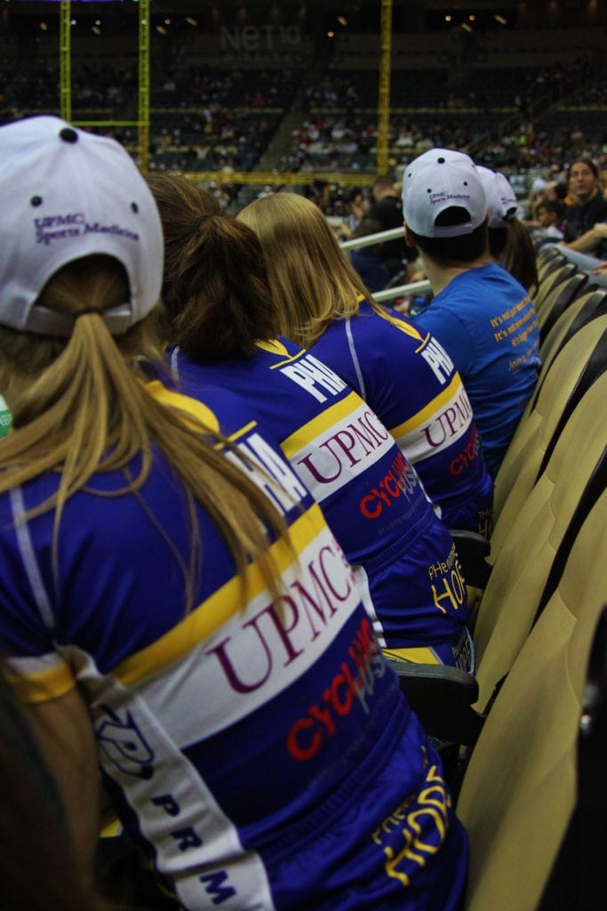 Members of Team PHenomenal Hope watching an indoor event, wearing their kit jerseys