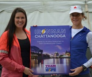 Monica and Amanada holding an Ironman Chattanooga Team PH sign