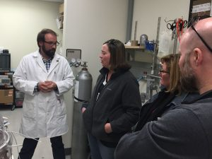 A UPMC man in a lab coat talking with others in a lab