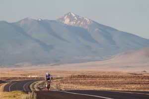 A lone Team PH rider racing beneath a massive mountain range