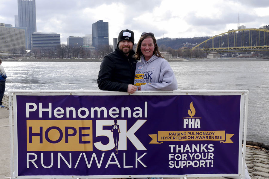 Race organizer Julia Feitner and her husband behind a Phenomenal Hope 5k race banner