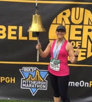 Beth Hamilton smiling after race ringing the bell